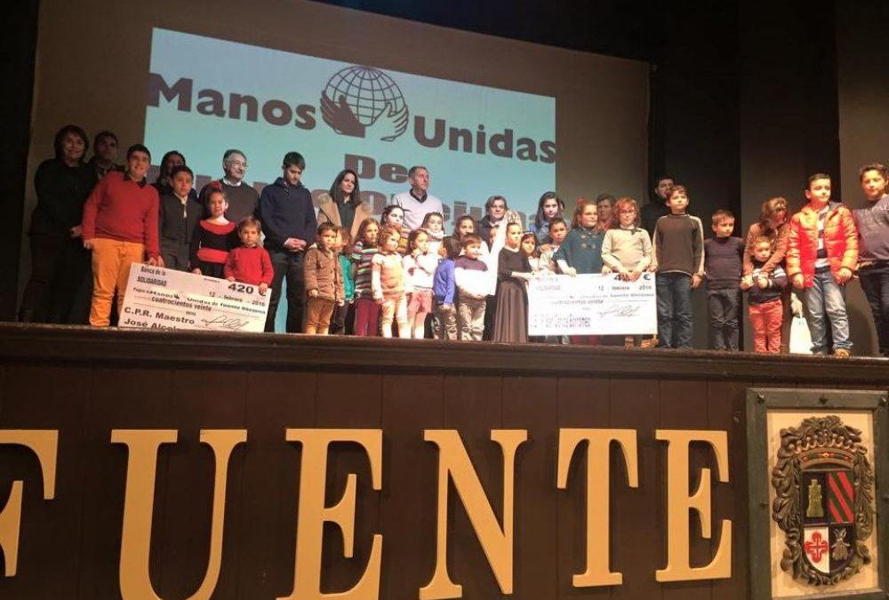 Escenario del teatro con niños portando cheques de dinero conseguido para Manos Unidas